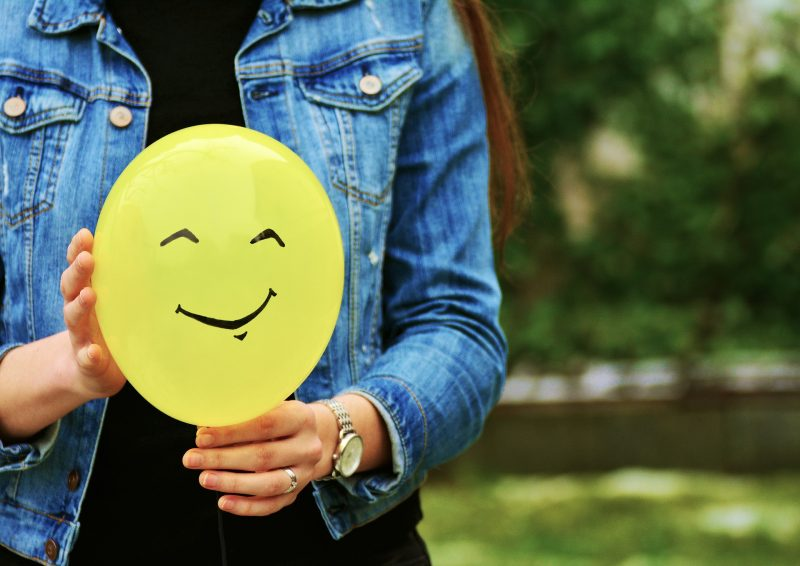 Woman holding balloon with smiley face on it