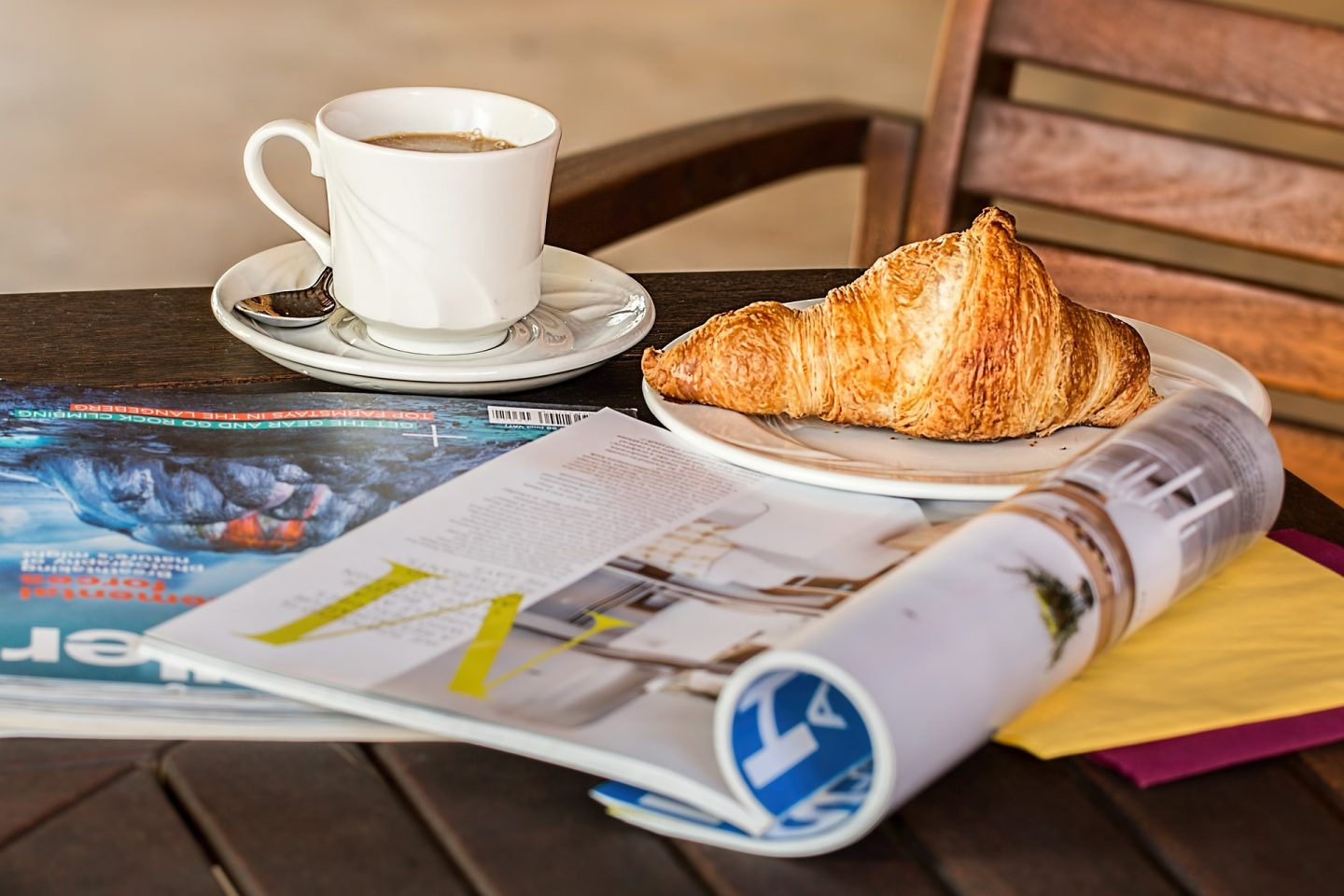 A relaxed morning with coffee, croissant and an open magazine