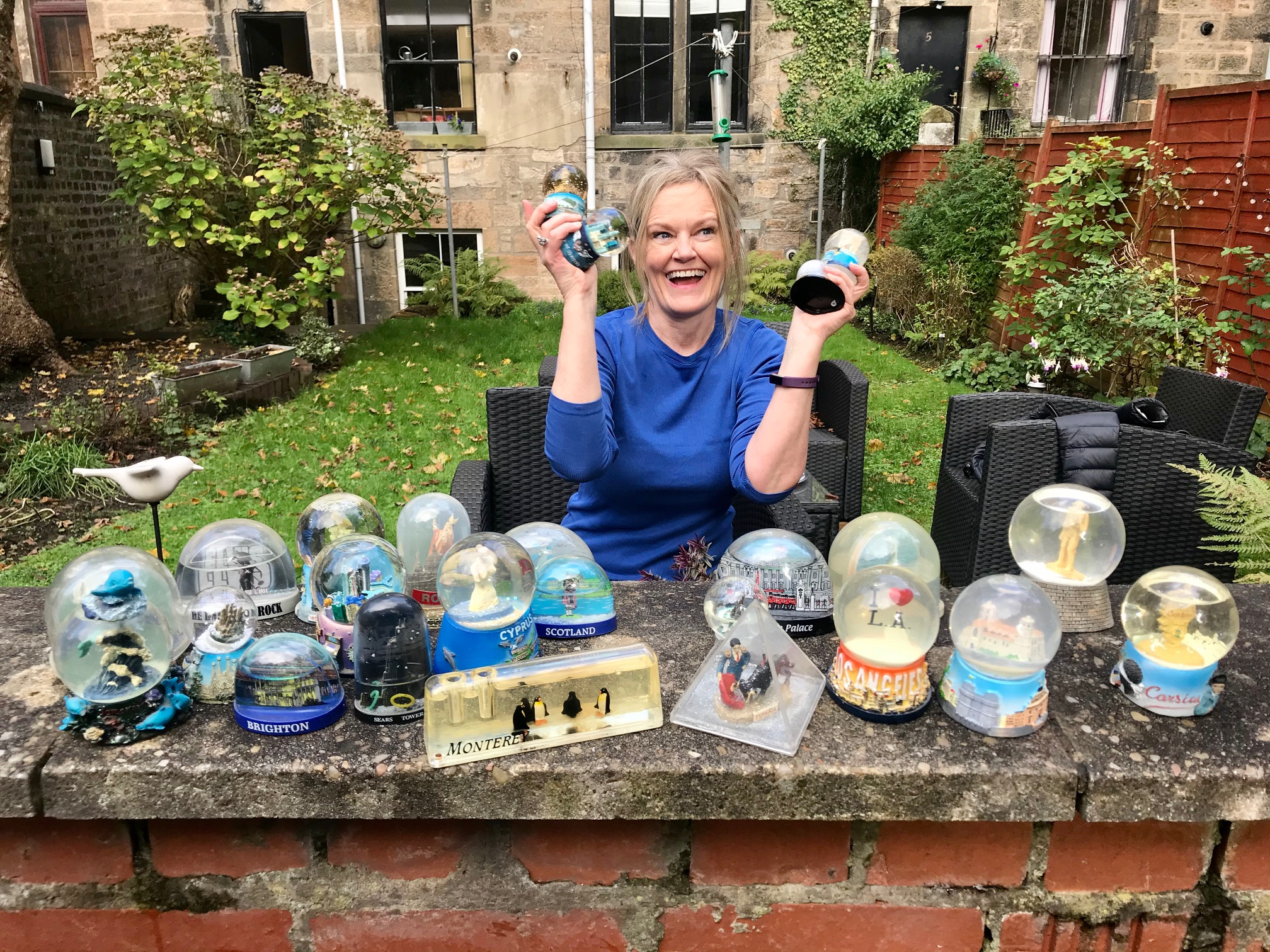 Attractive woman surrounded by her collection of Snow Globes