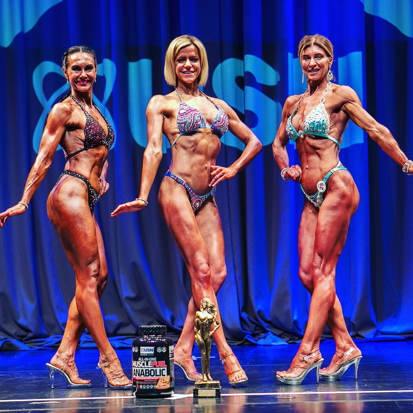 Three Body Building Champions posing on stage
