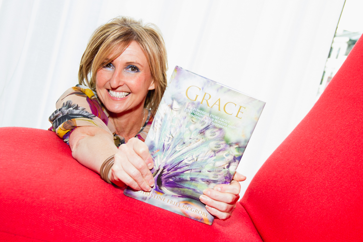 Christine, founder of The Key, holds her book, Grace