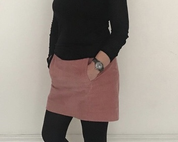 A woman with her hands in the pocket of her skirt