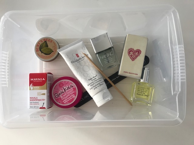 box of manicure products in including hand cream and nail oil