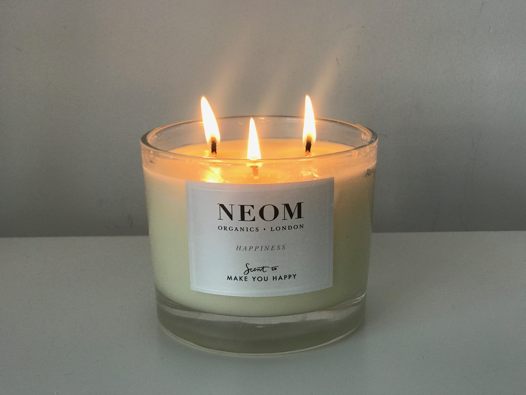 A lit NEOM candle - 1 of 8 Lockdown Must-Haves